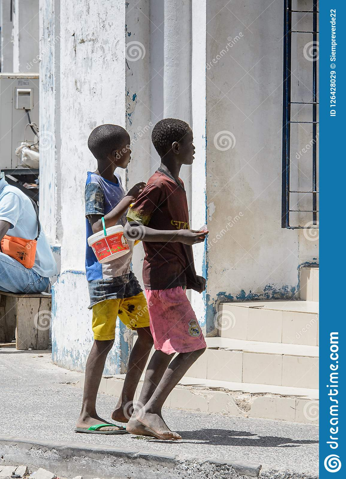 Unidentified Senegalese two boys walk along the street in the c