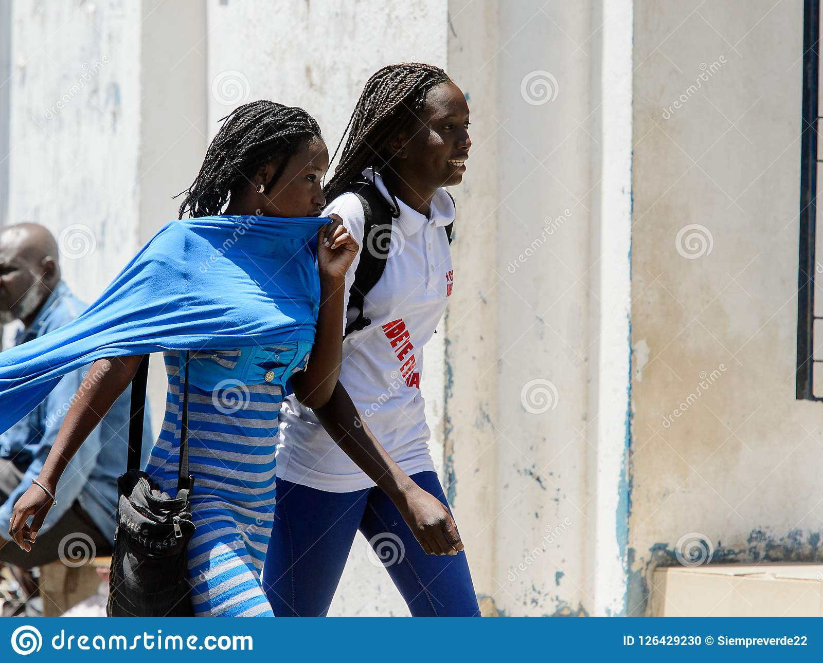 Unidentified Senegalese women walk along the street in the cent