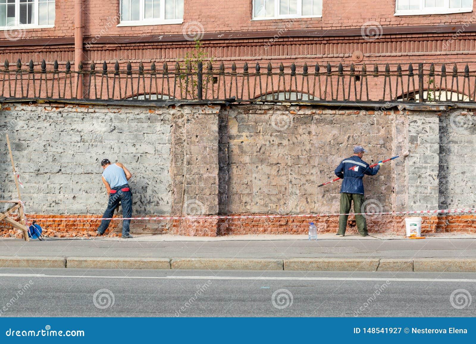 Saint Petersburg, Russian Federation-Aug 16 2018: workers repairing a brick fence