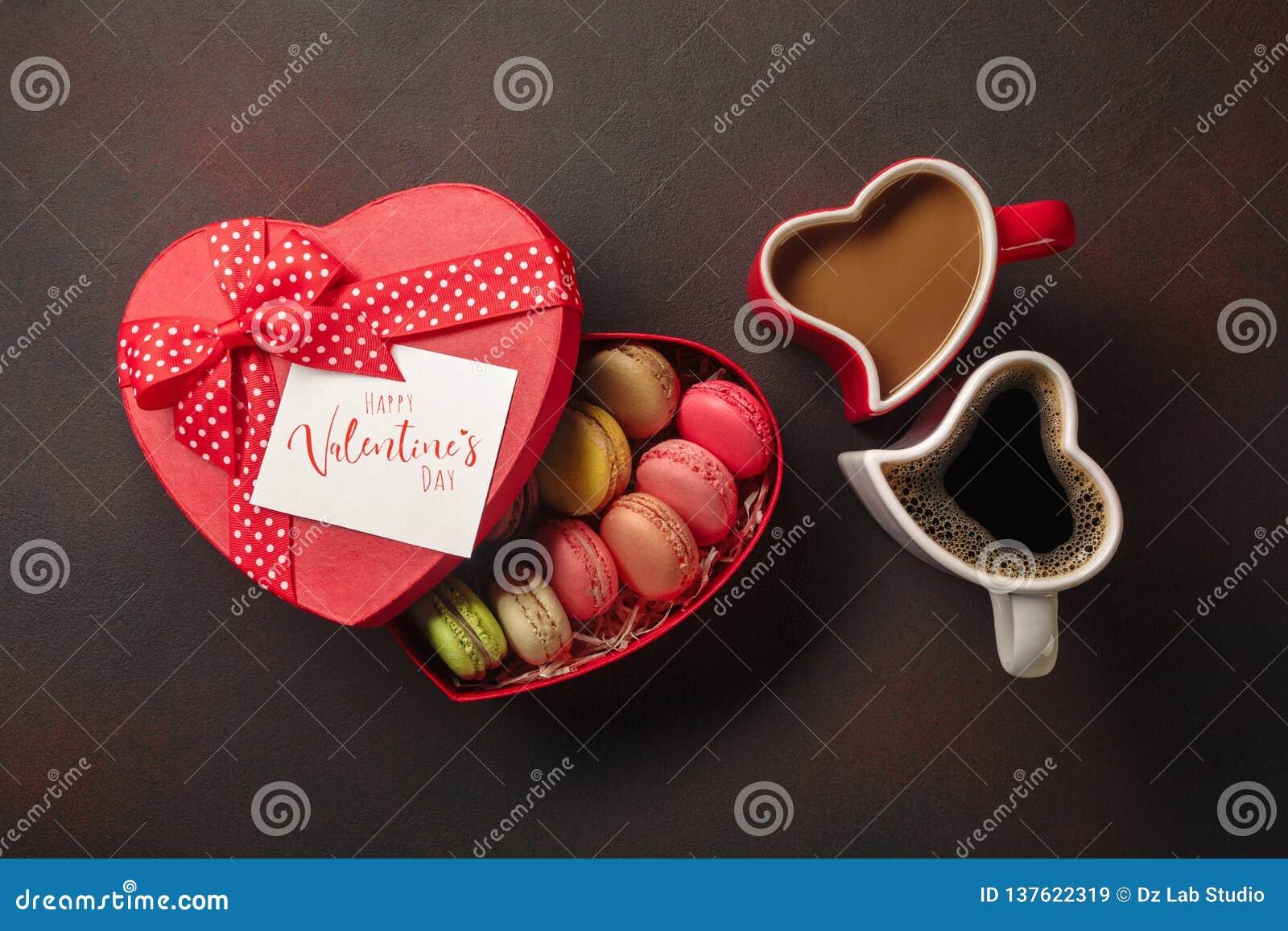 Saint-Valentin avec des cadeaux, une boîte en forme de coeur, des tasses de café, des biscuits en forme de coeur, des macarons et