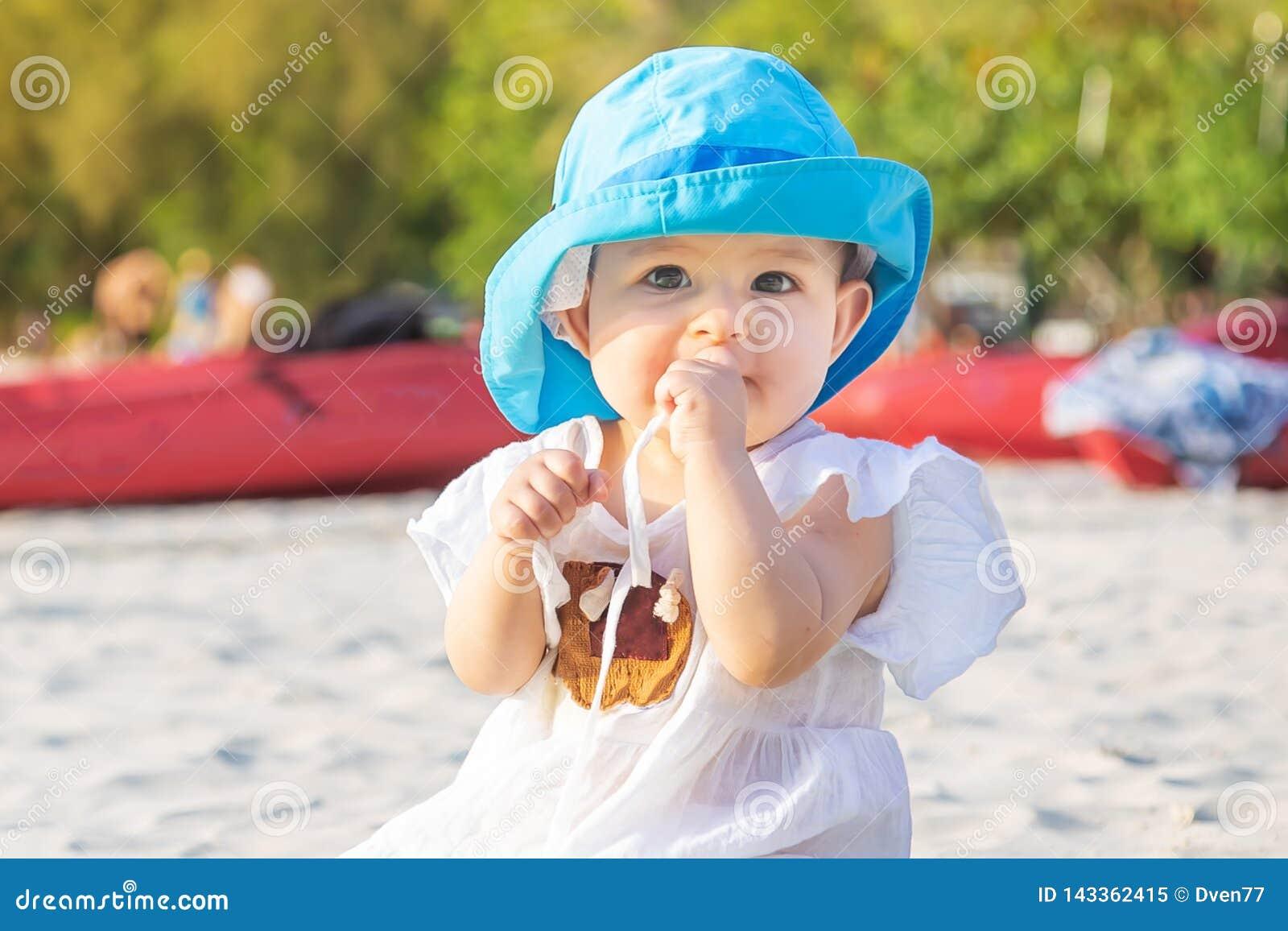 Sair os dentes em 8 meses Bebê que senta-se na praia e nas mastigações um teether No chapéu azul e no vestido branco na esteira d