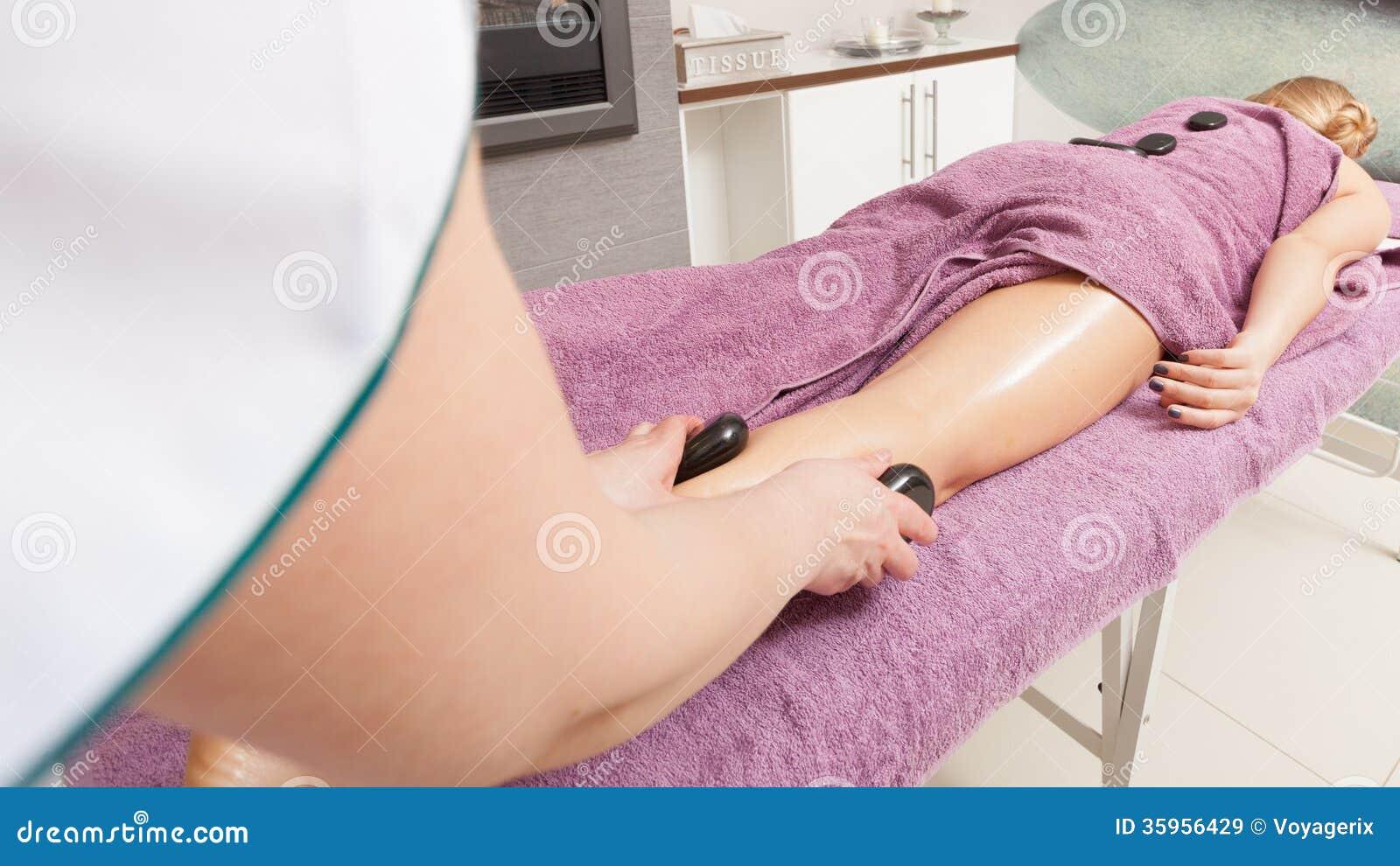 Salón de belleza. Mujer que consigue a balneario masaje de piedra caliente de las piernas
