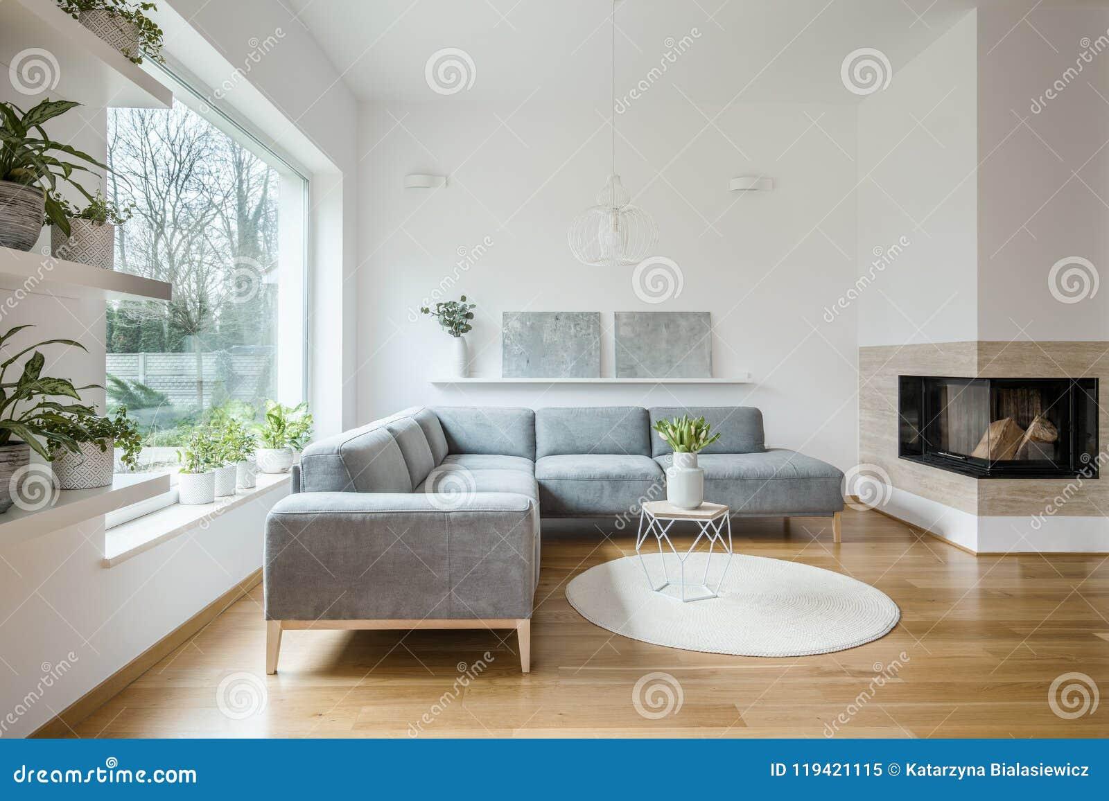 Salón de la esquina gris que se coloca en el interior blanco de la sala de estar con dos pinturas del arte moderno en el estante,