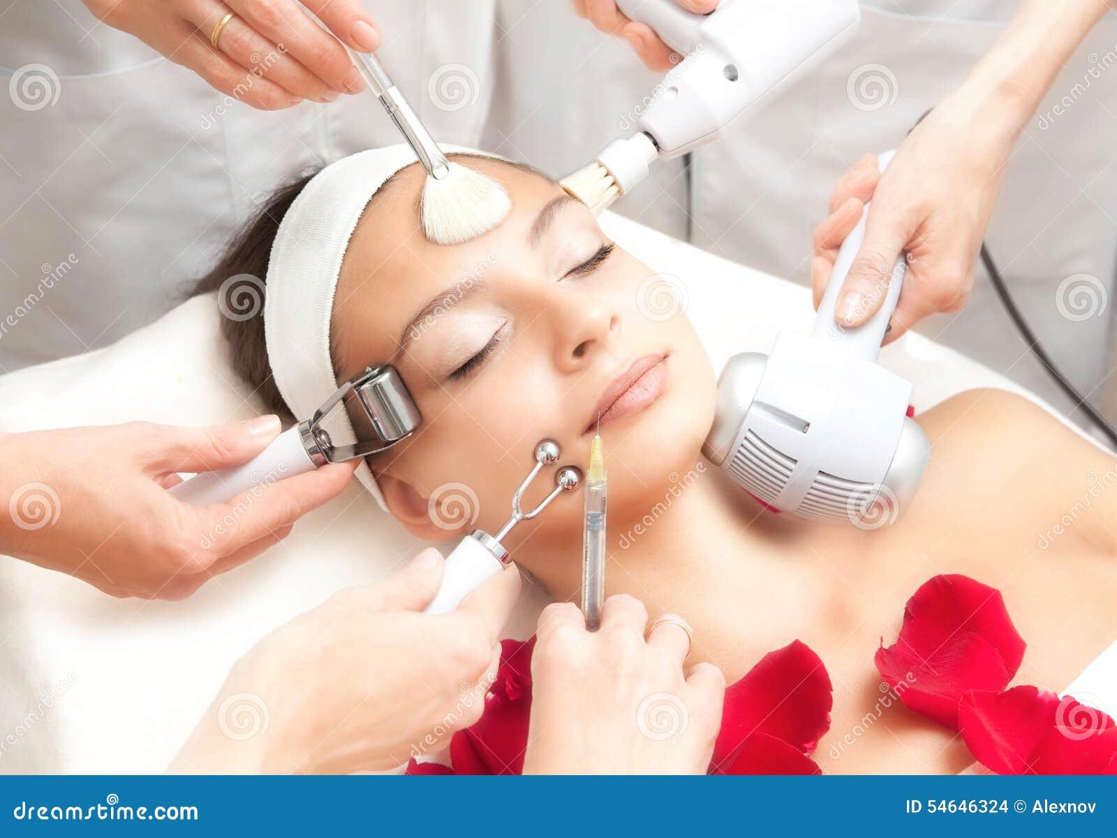 Salón del balneario: Mujer hermosa joven que tiene diverso tratamiento facial