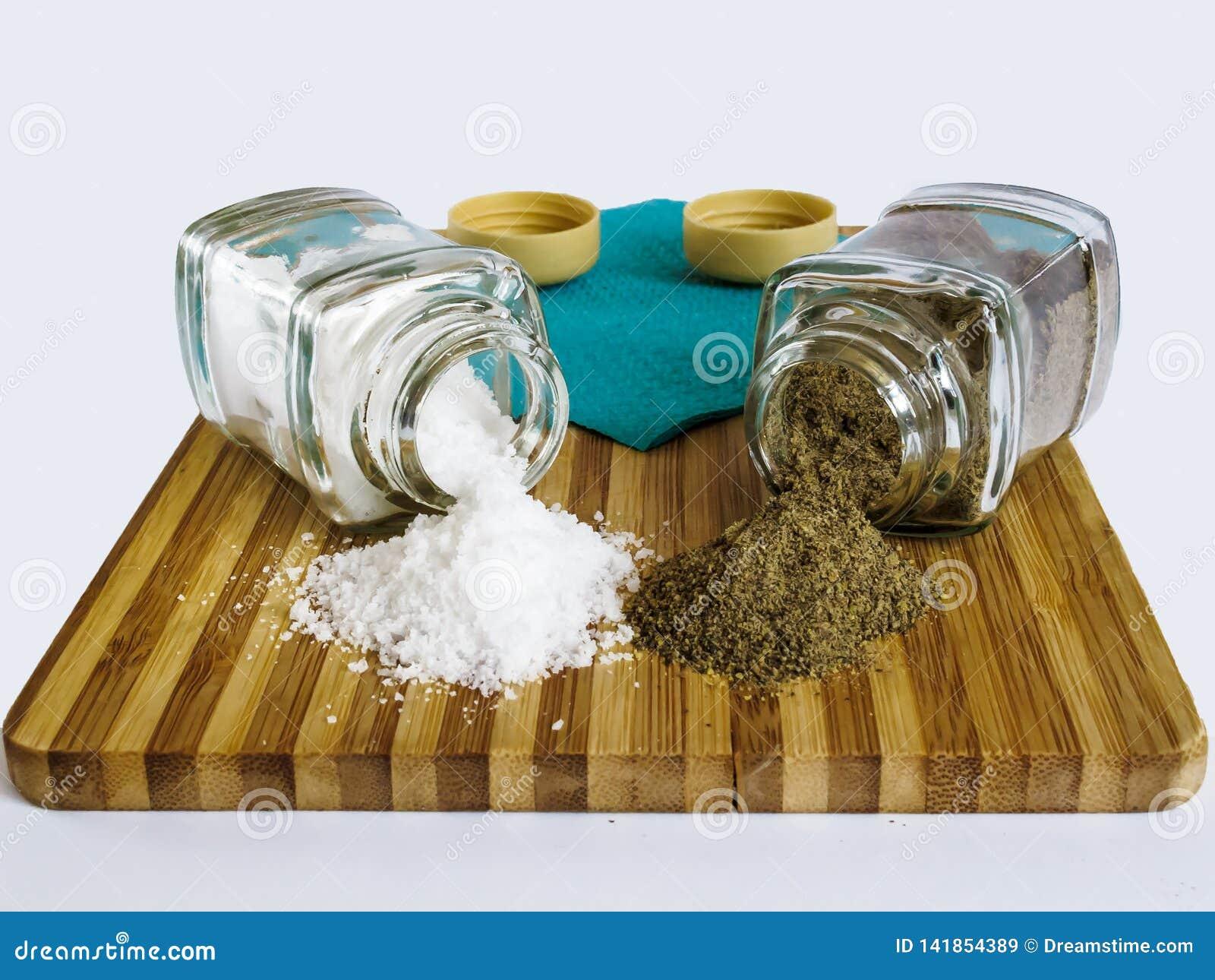 Sal y pimienta dispersadas de las coctelera de sal de cristal y de las coctelera de la pimienta en una tabla de cortar