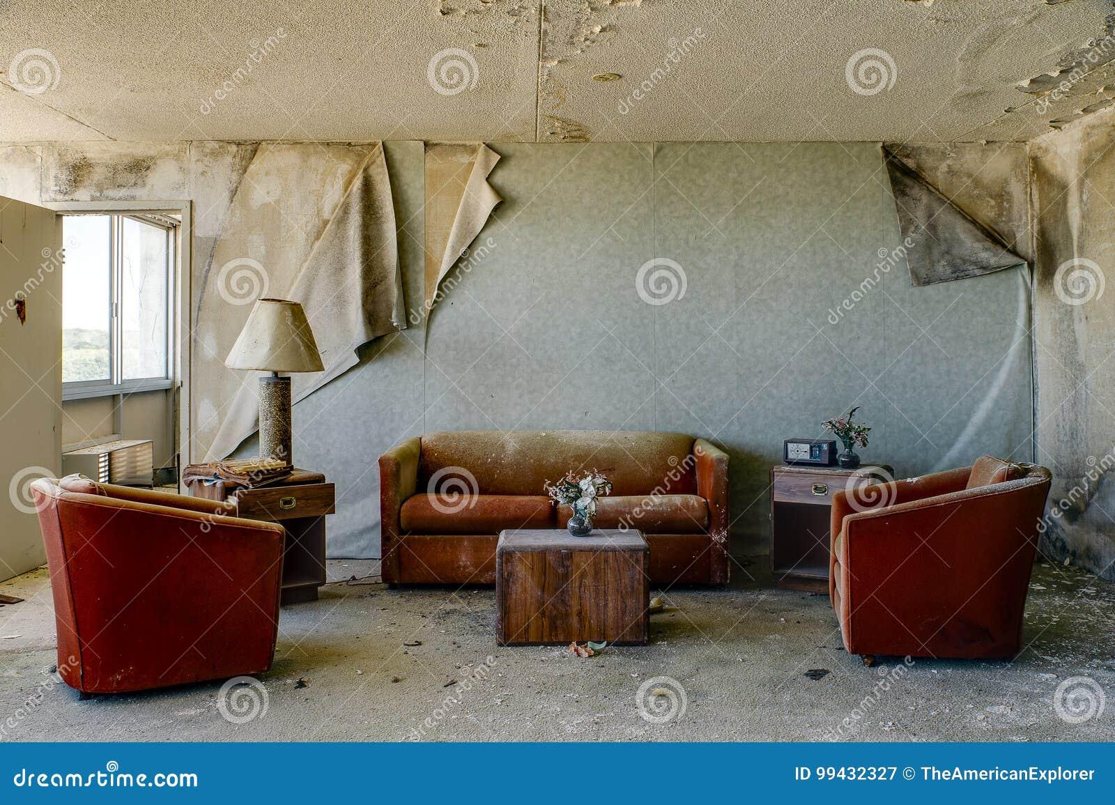 Sala de alojamento intacto com as cadeiras & o sofá alaranjados queimados - hotel abandonado