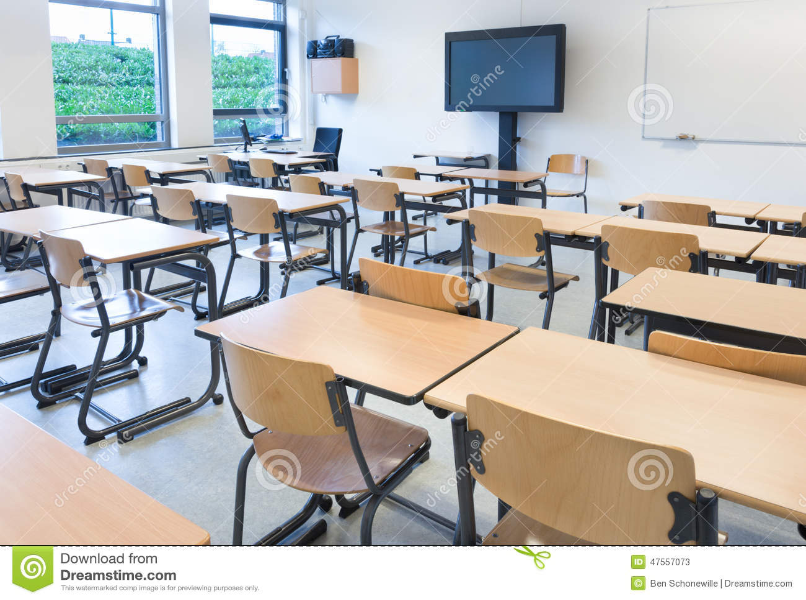 Sala de clase vacía con las tablas y las sillas