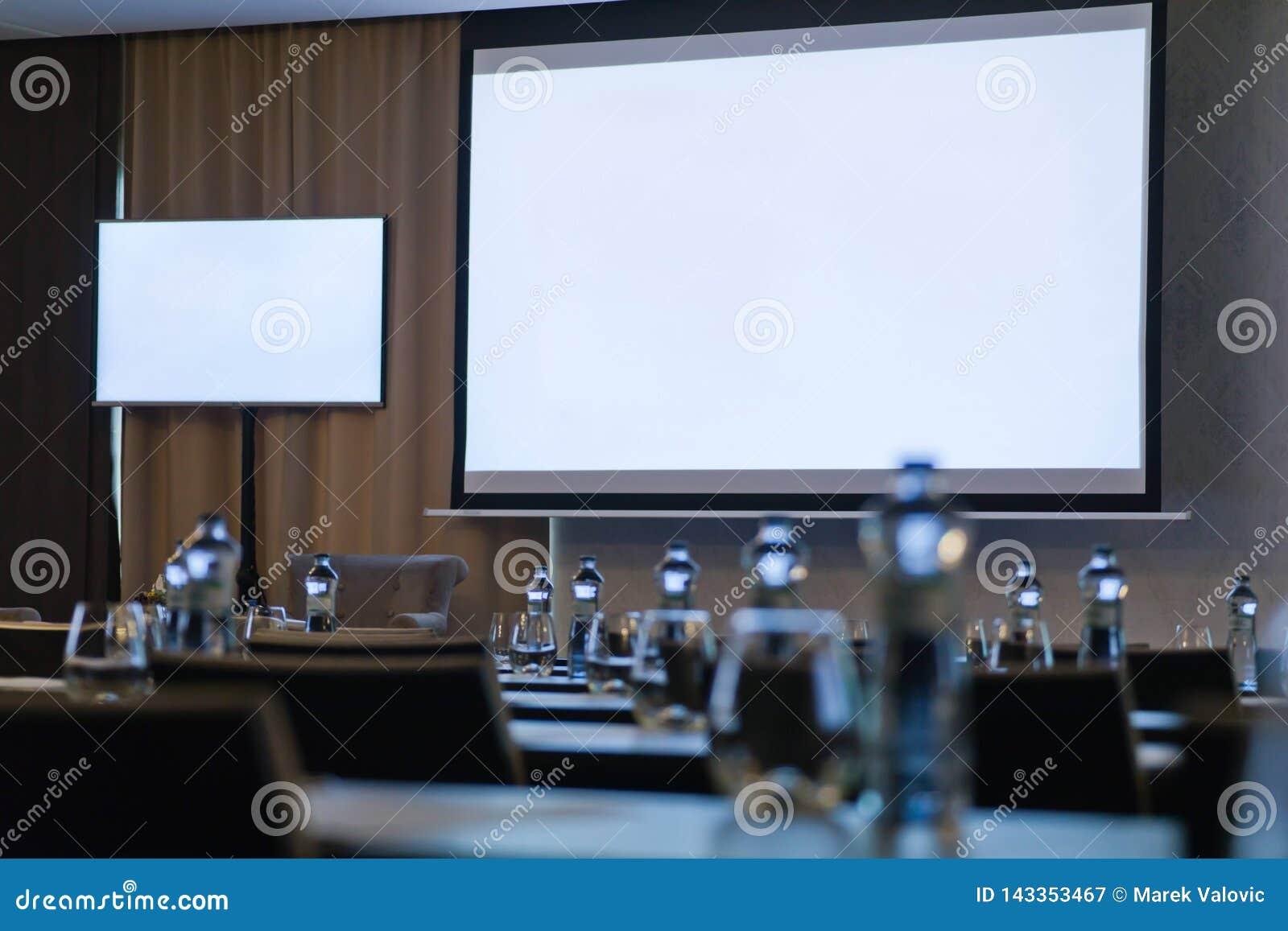 Sala de conferências com as duas telas brancas vazias Garrafas fora de foco