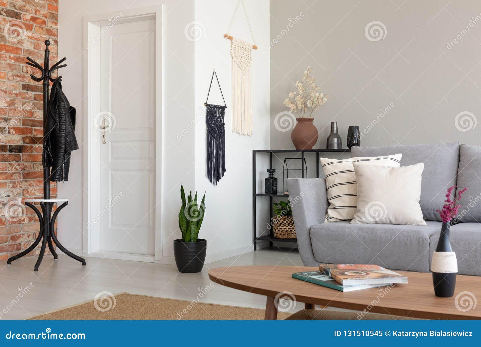 Sala de estar elegante con el sofá gris y la tabla de madera, foto real