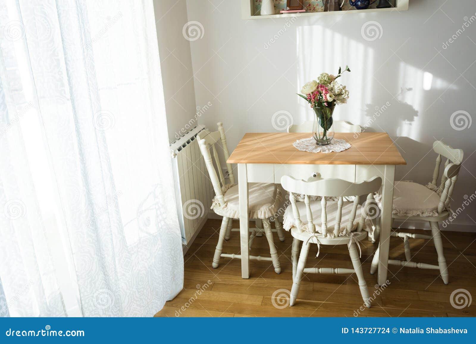 Sala de vida agradavelmente decorada do almoço Mesa de jantar e algumas cadeiras