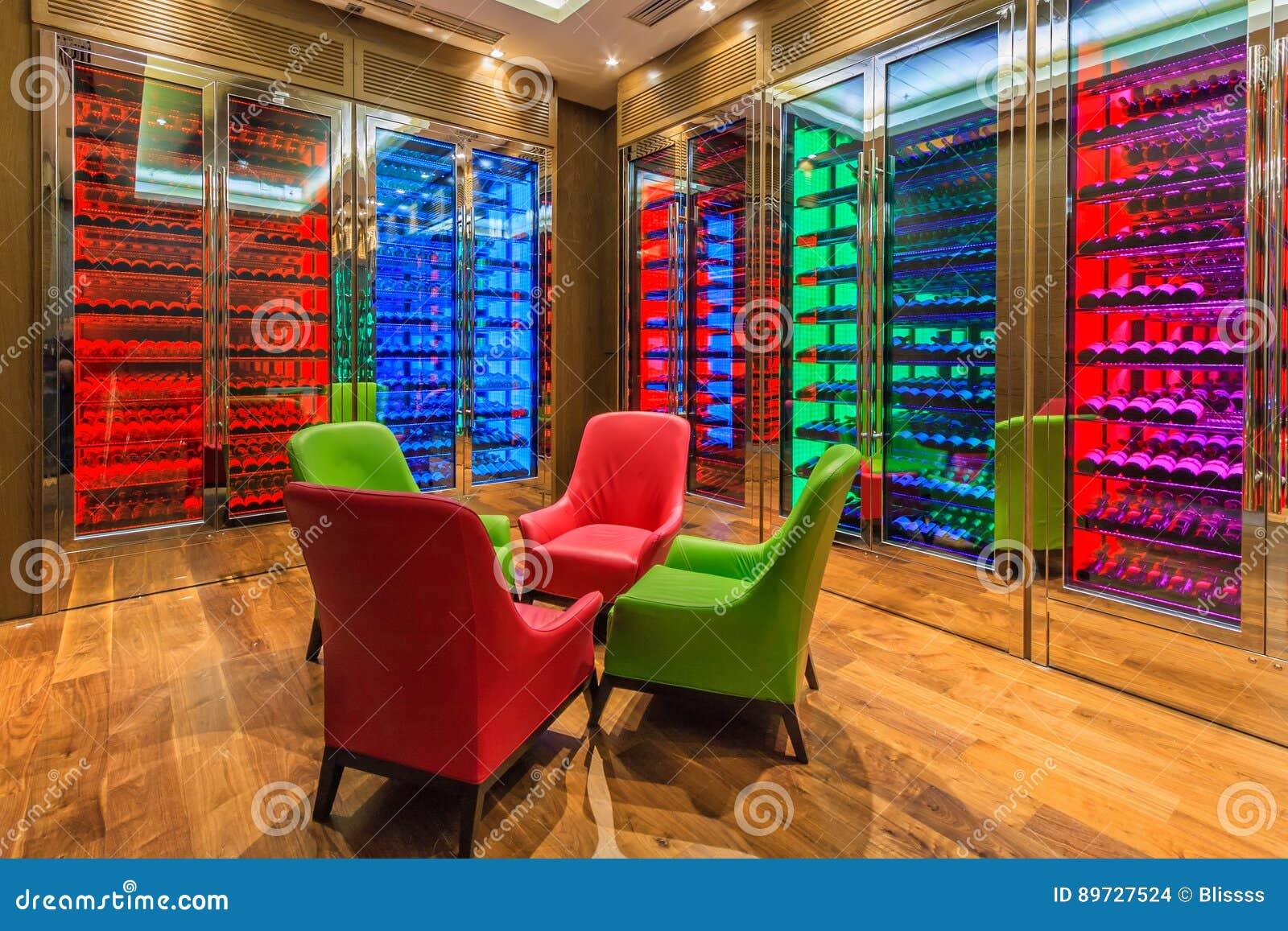 A sala do vinho do hotel de Solis Sochi é executada no estilo moderno com a iluminação colorida Muitas garrafas de vinho encontra