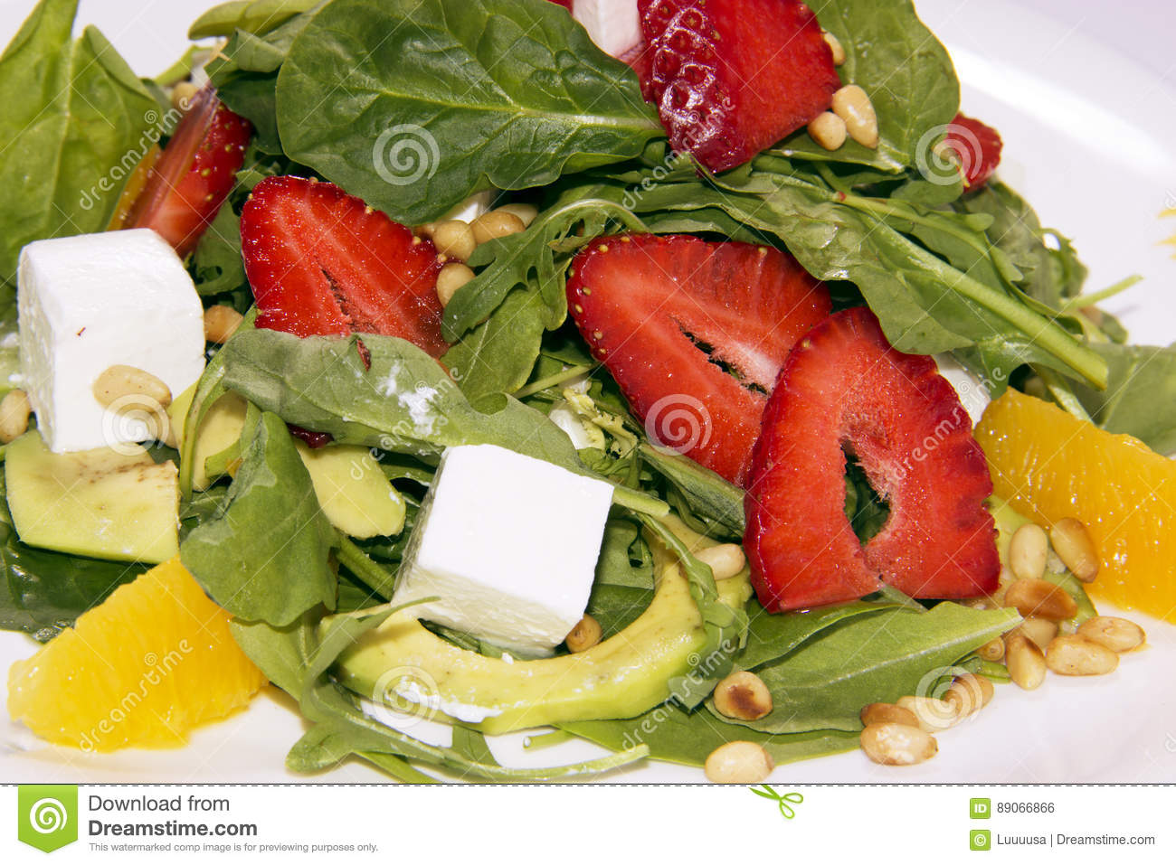 Salad with arugula,strawberries and cheese. background salad texture