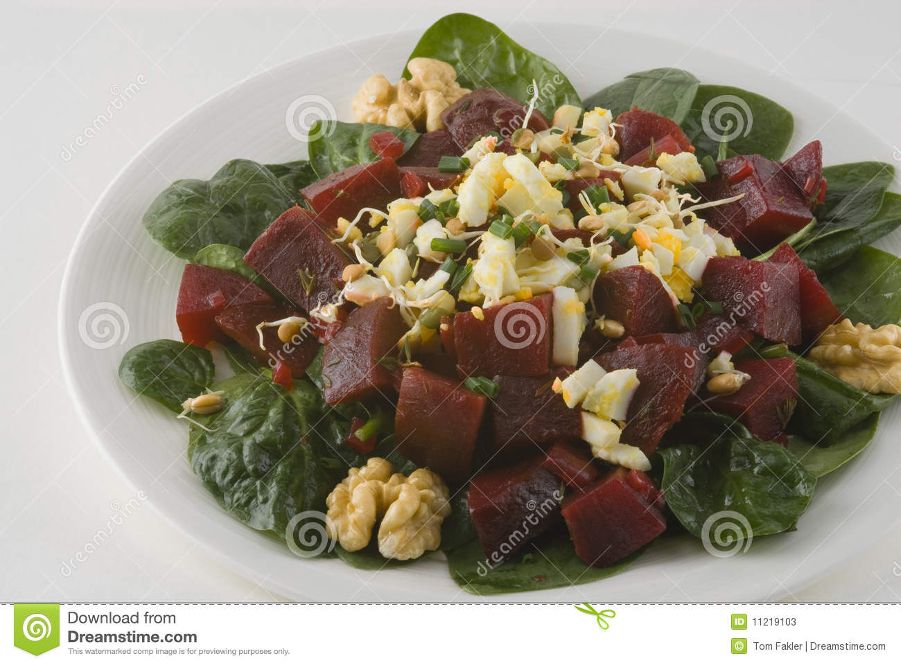 Salad with beets, boiled egg, and bean sprouts, walnuts on a bed of ...