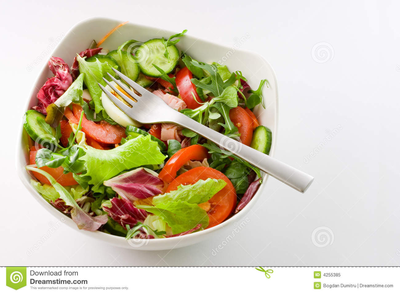 Top view of white bowl of mixed vegetables salad on white background.