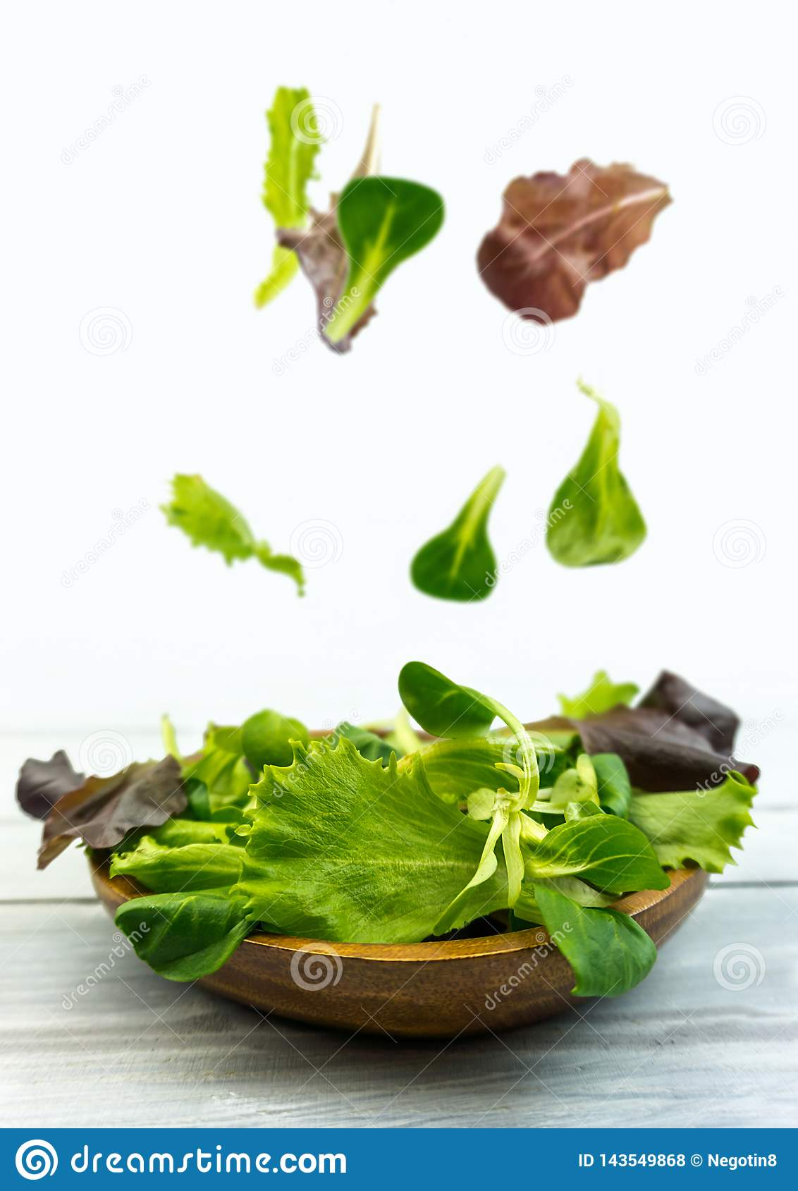 Salad explosion with arugula, beetroot, spinach and sprouts on bright wooden board