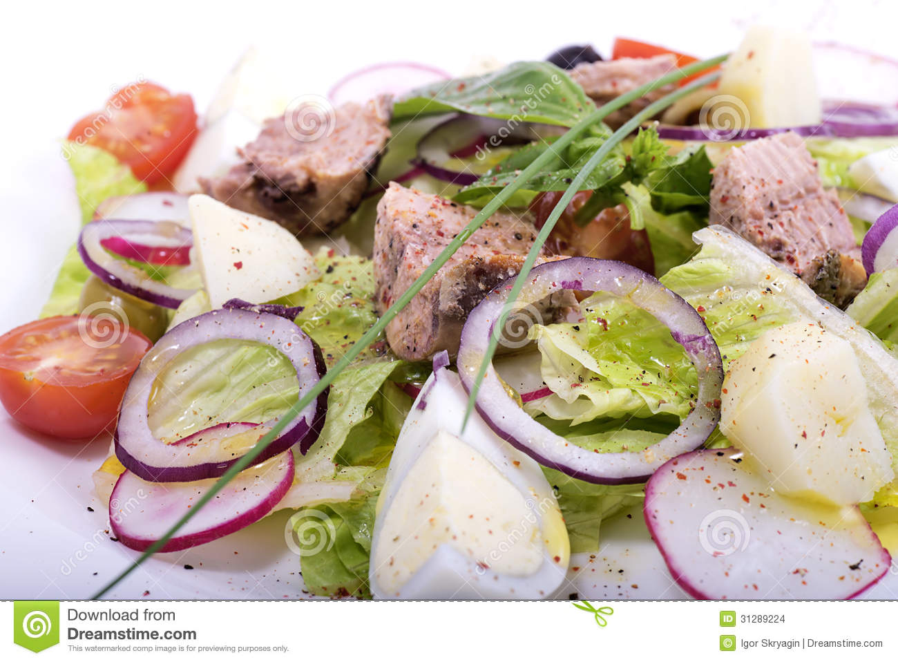 Salad from fresh vegetables with fish on a white dish close up.