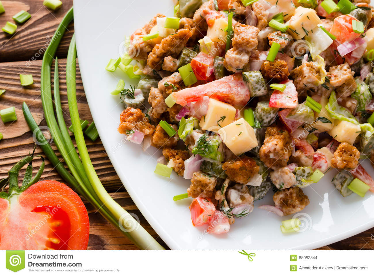 Salad with mayonnaise close to the green onions and half a tomato