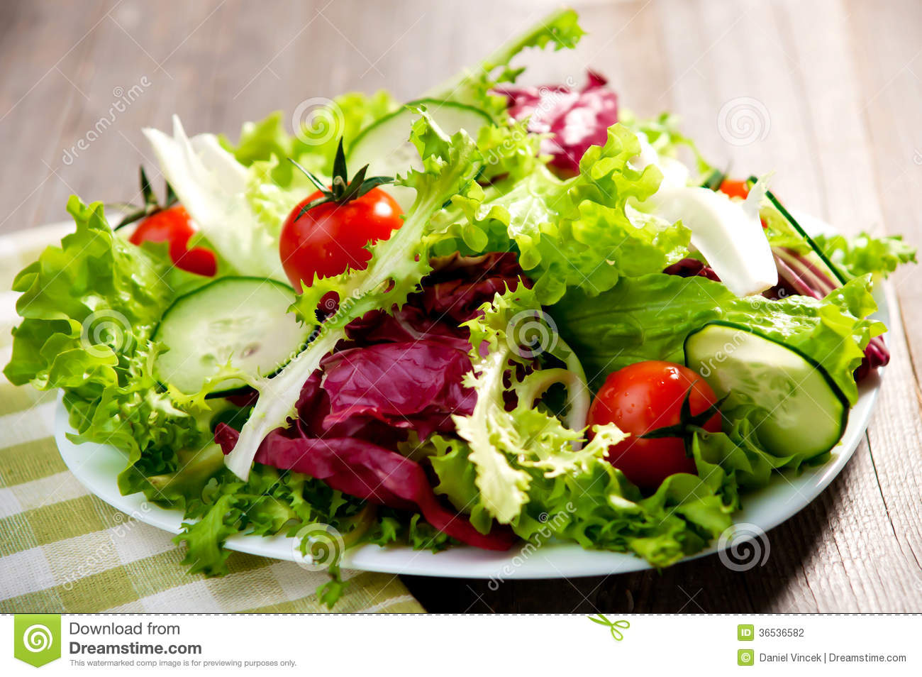 Mix salad with fresh vegetable on wood table.