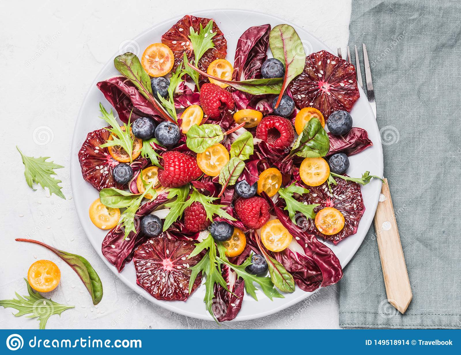 Salad plate with greens, oranges and berries top view. Healthy raw food concept.