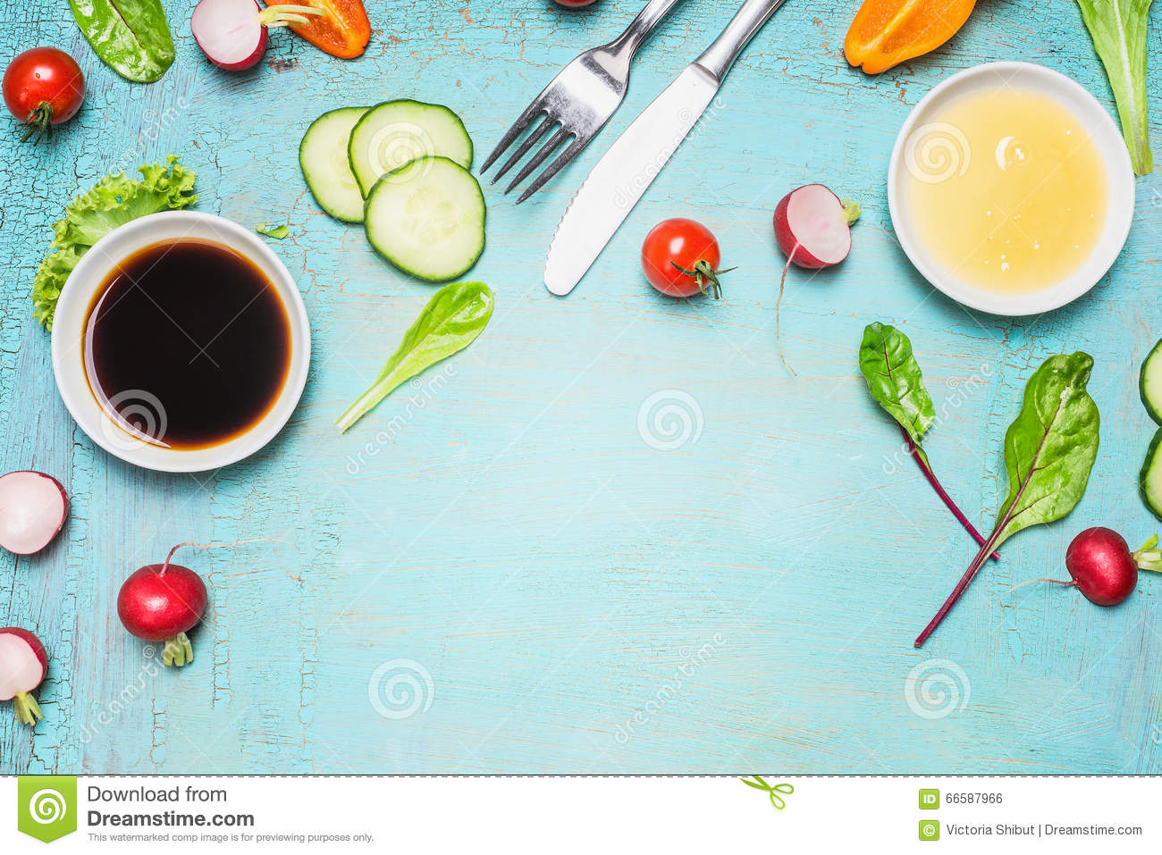 Salad preparation with cutlery dressing ingredients , lettuce , herbs and vegetables on light blue wooden background, top view