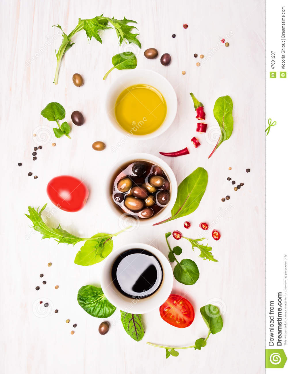 Salad preparation with dressings,olives, wild herbs leaves, chili, oil and tomatoes