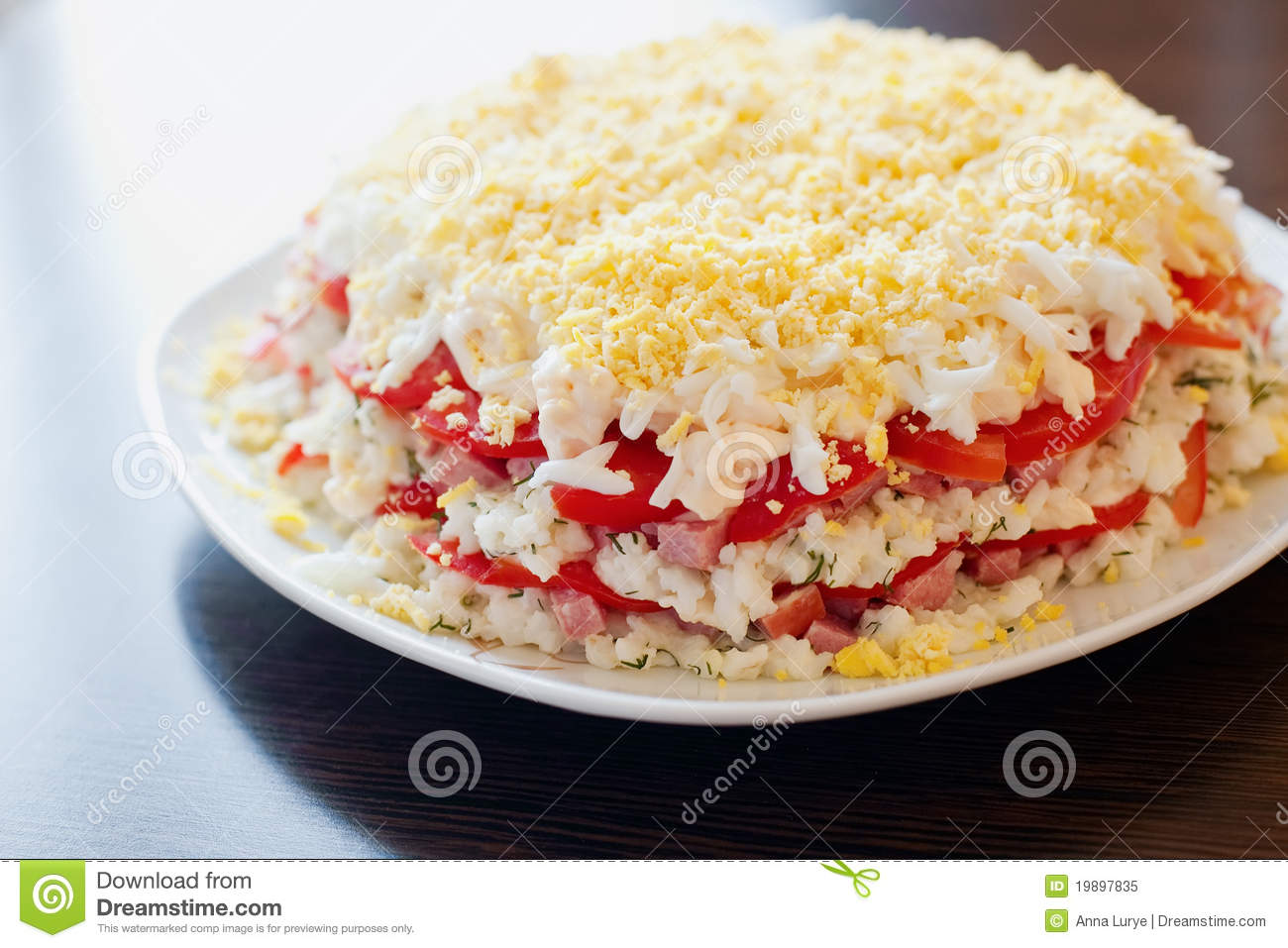 Close-up salad made with layers of rice, tomatoes, sausage, cheese and ...