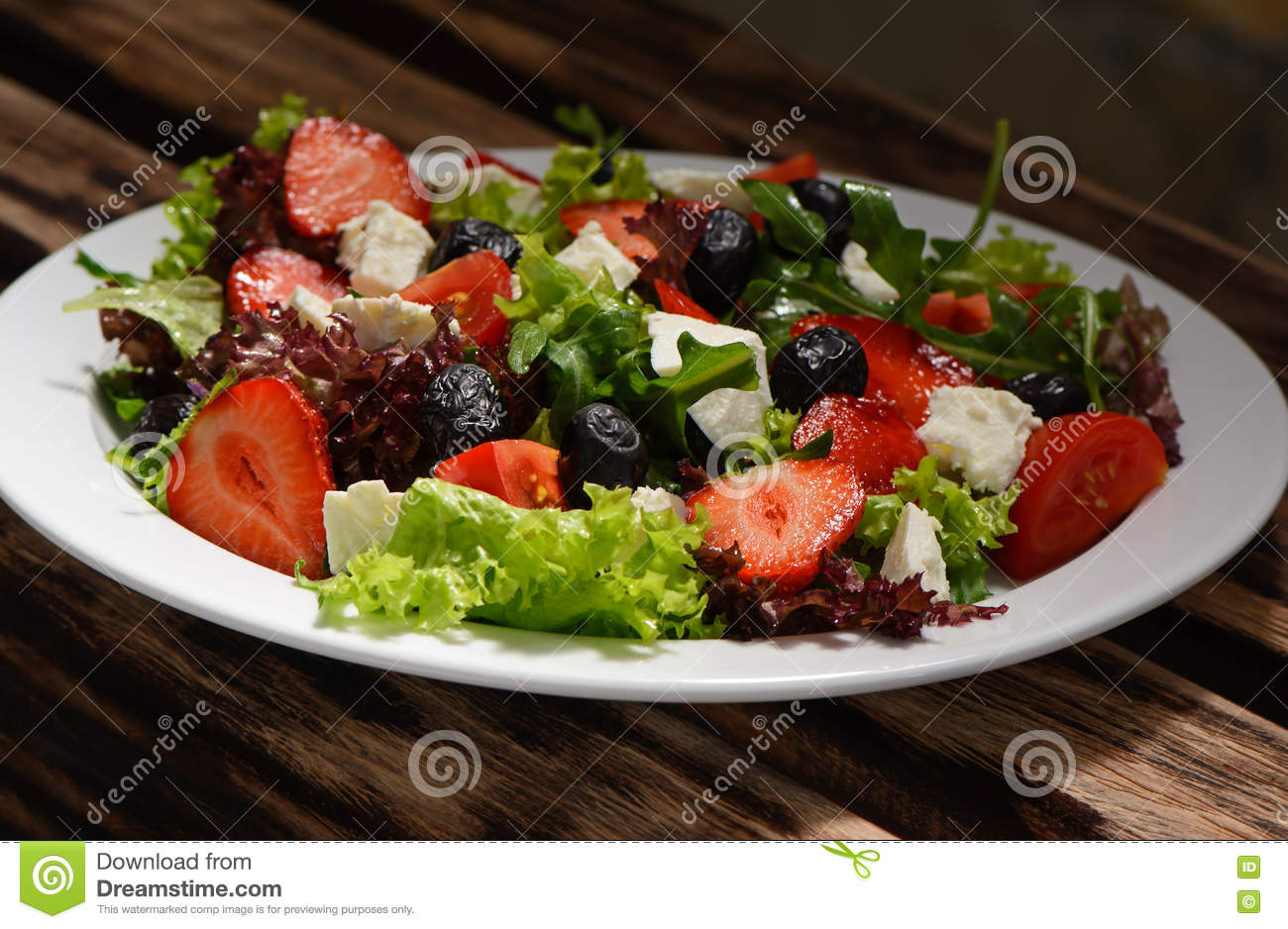 Salad, strawberries, cheese, tomatoes, olives