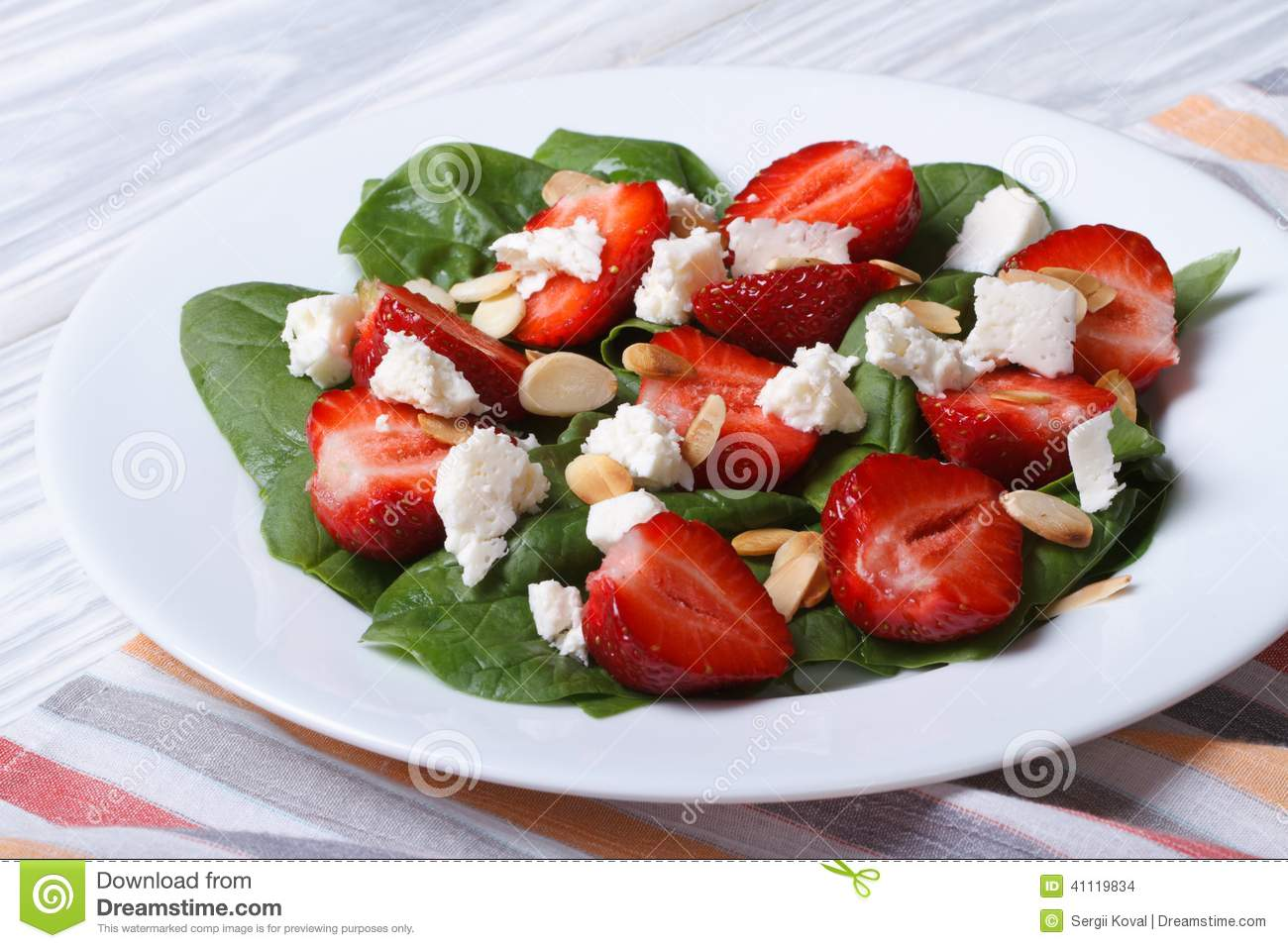 Salad with strawberries, spinach and goat cheese on a white plate on ...