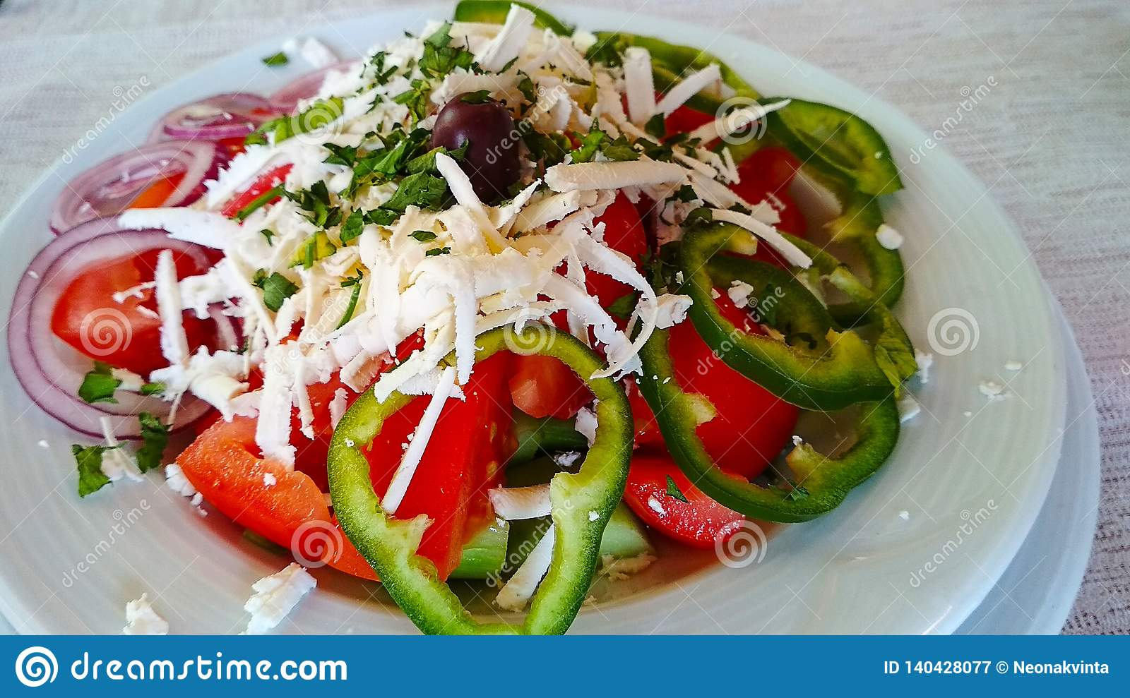 Salad in a white plate with onion, olives and grated cheese