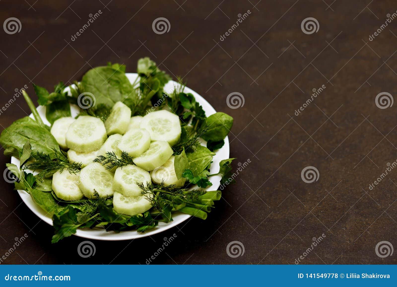 Salada com legumes frescos, ervas, e pepinos no fundo preto com espaço da cópia
