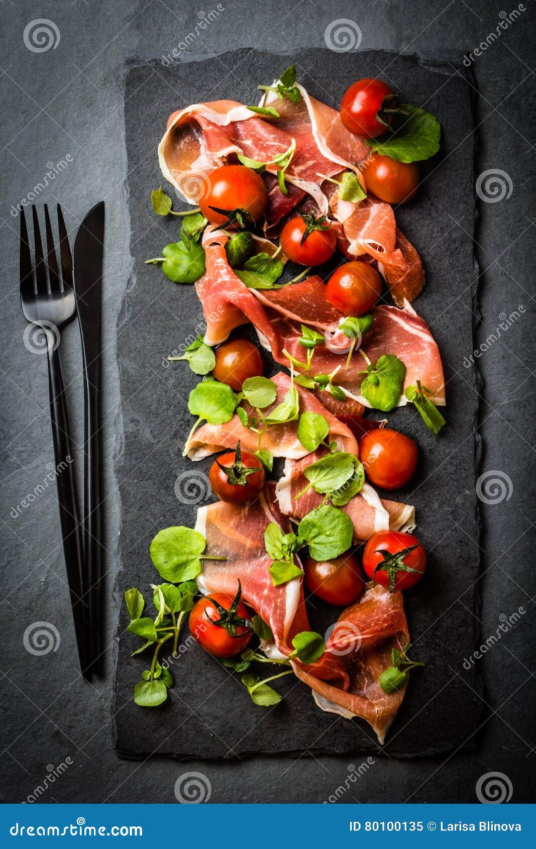 Salada com o serrano do jamon do presunto, tomates de cereja, rúcula, placa da ardósia