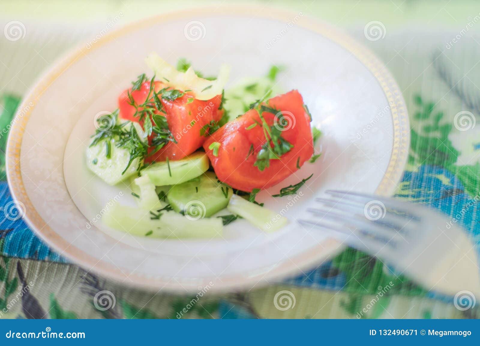 Salada com tomate, o pepino, pimento e verdes frescos em uns pires brancos com uma forquilha