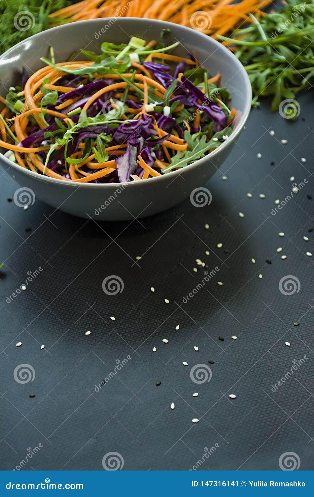 Salada da couve vermelha, das cenouras e dos verdes Decorado com vegetais e as ervas cortados Cortando tiras Fundo escuro