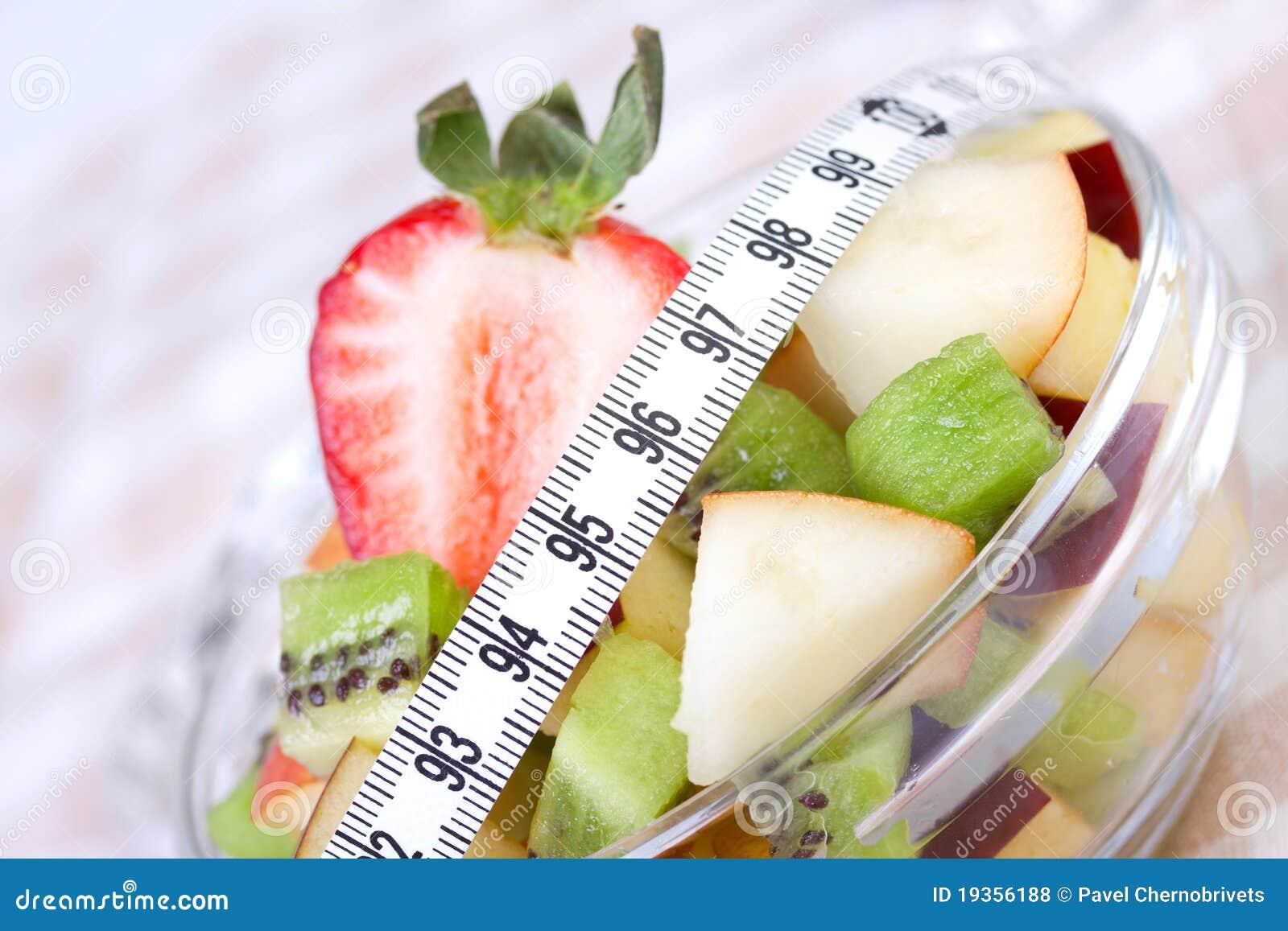 Salada de fruta na placa branca com fita da medida