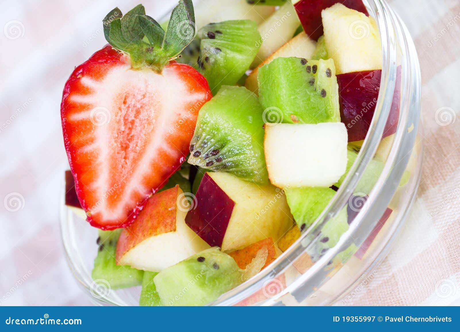 Salada de fruta na placa branca no tablecloth