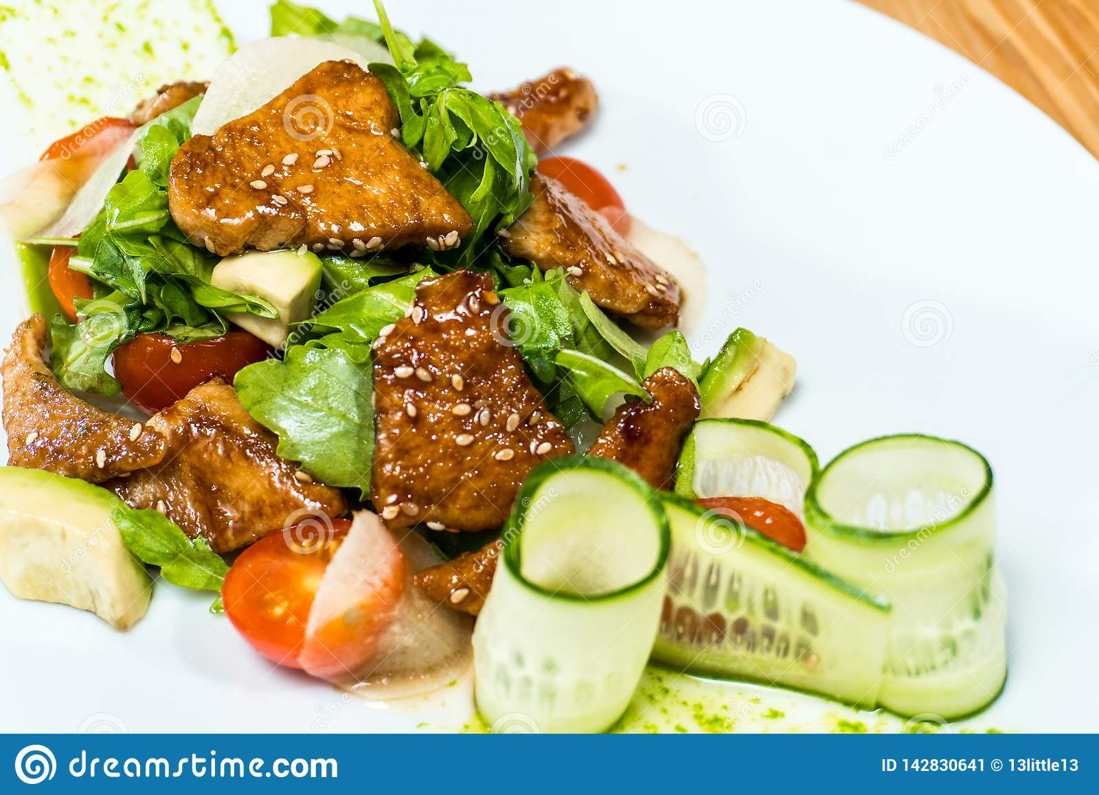 A salada de pepinos e de tomates frescos fritou a carne em uma tabela de madeira
