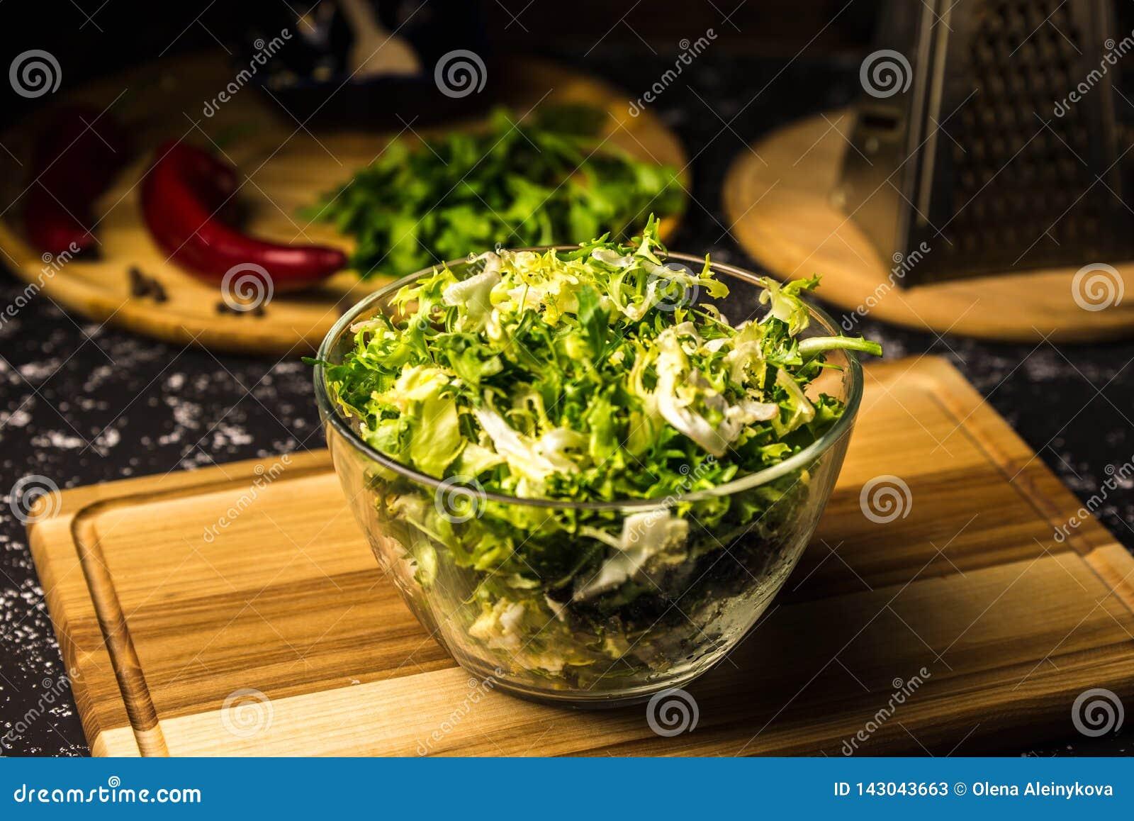 Salada do couve-de-bruxelas em uma bacia de vidro em uma placa de madeira