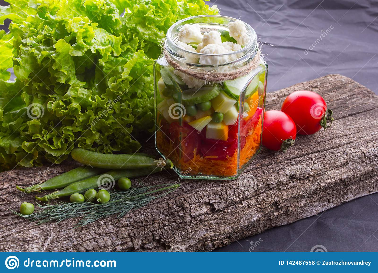 Salada do legume fresco com ervas em uma placa de madeira, fundo textured preto