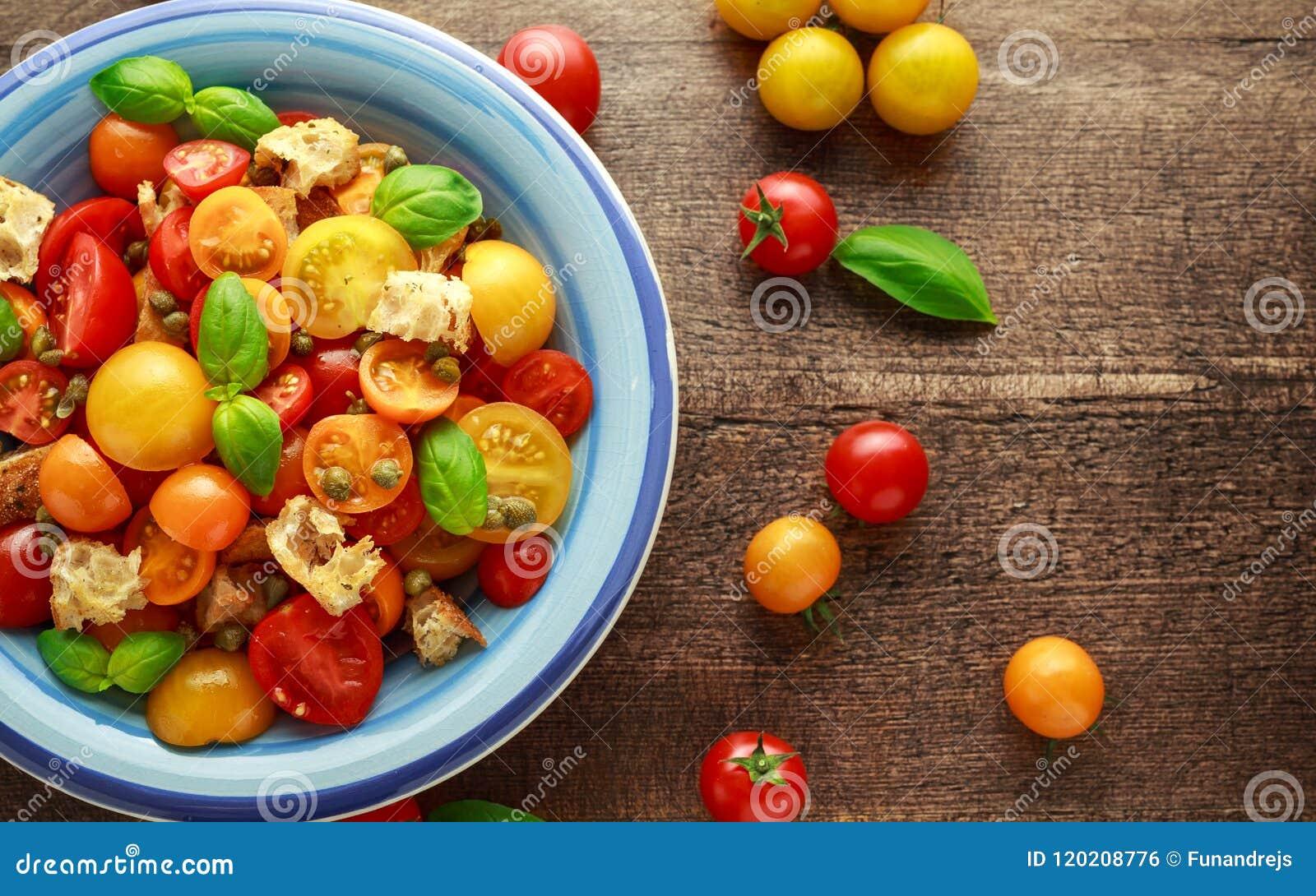 Salada do tomate de Panzanella com os tomates de cereja, as alcaparras, manjericão e o pão torrado vermelhos, amarelos, alaranjad