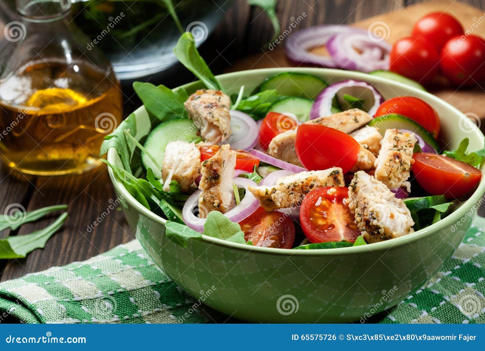 Salada fresca com galinha, tomates e rúcula na placa