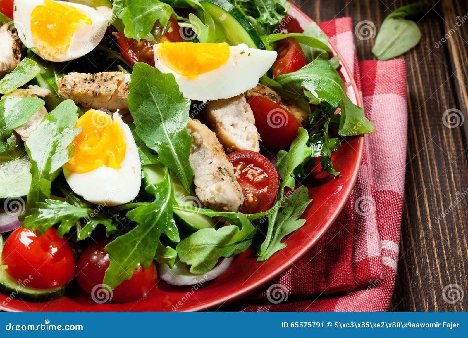 Salada fresca com galinha, tomates, ovos e rúcula na placa