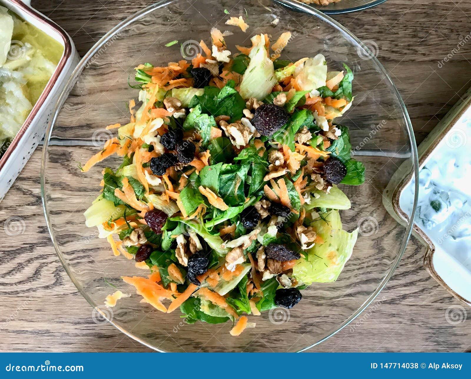 Salada fresca da noz com fatias raspadas da cenoura na bacia de vidro na tabela de jantar