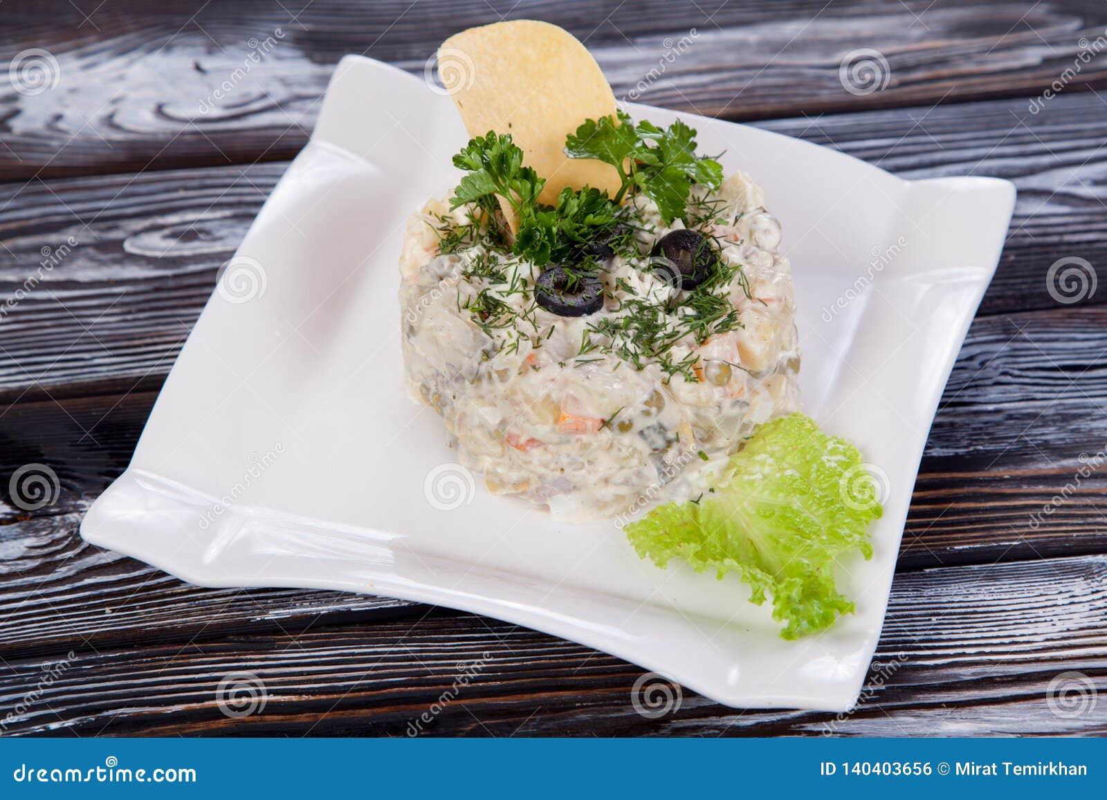 Salada fresca do russo delicioso com verdes, na tabela