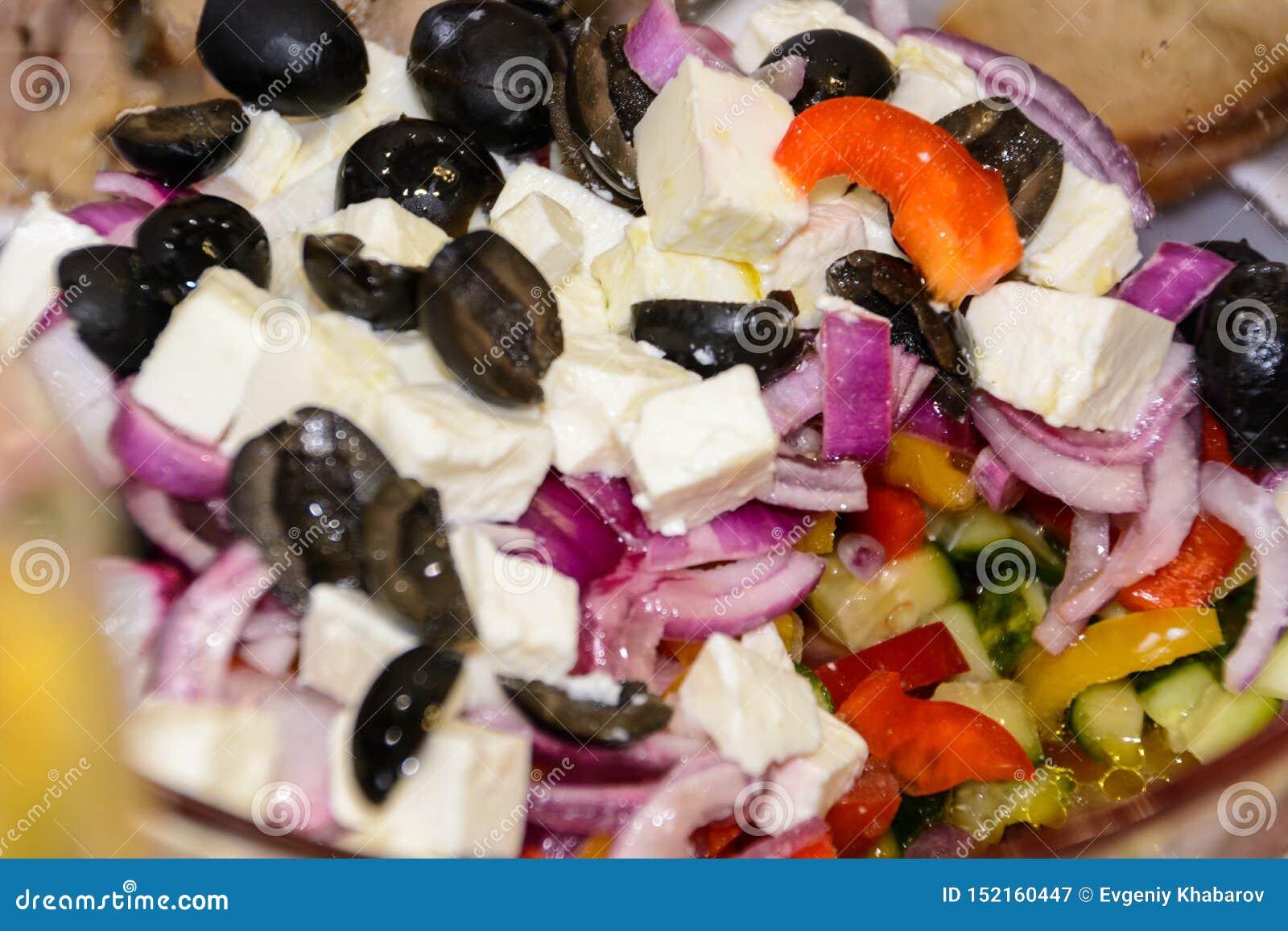 Salada grega, no close-up Tomates, azeitonas pretas, cebolas vermelhas, pepino, alecrins, pimenta doce, queijo de feta e azeite