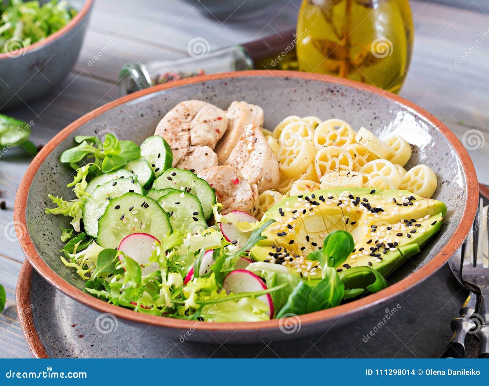 Salada saudável com galinha, abacate, pepino, alface, rabanete e massa no fundo escuro Nutrição apropriada Menu dietético