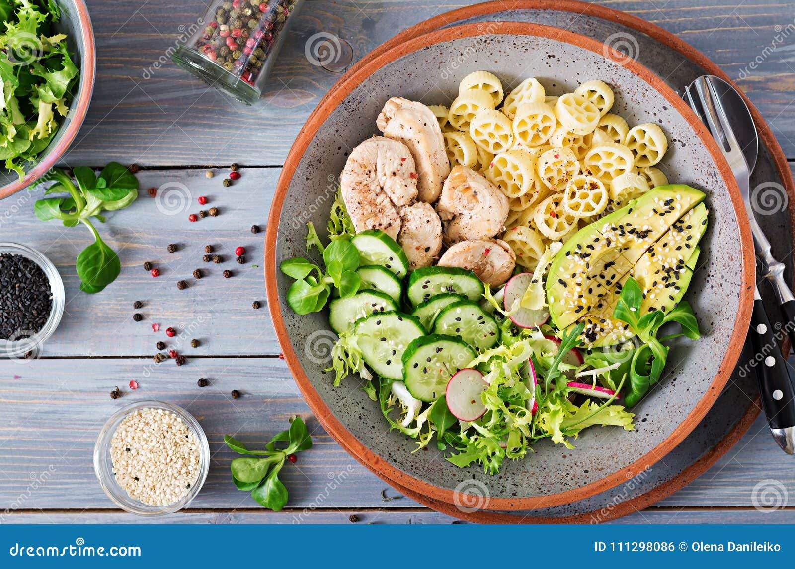 Salada saudável com galinha, abacate, pepino, alface, rabanete e massa no fundo escuro Nutrição apropriada Menu dietético Dinn