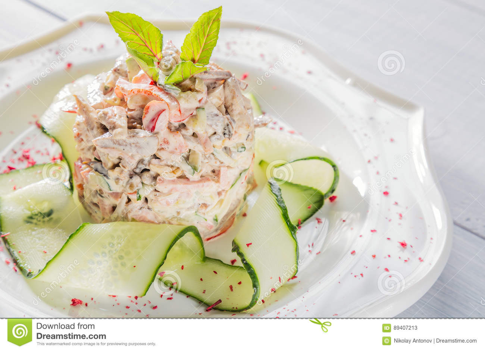 Salada vegetal com carne, ervas, pepino e especiarias na placa branca