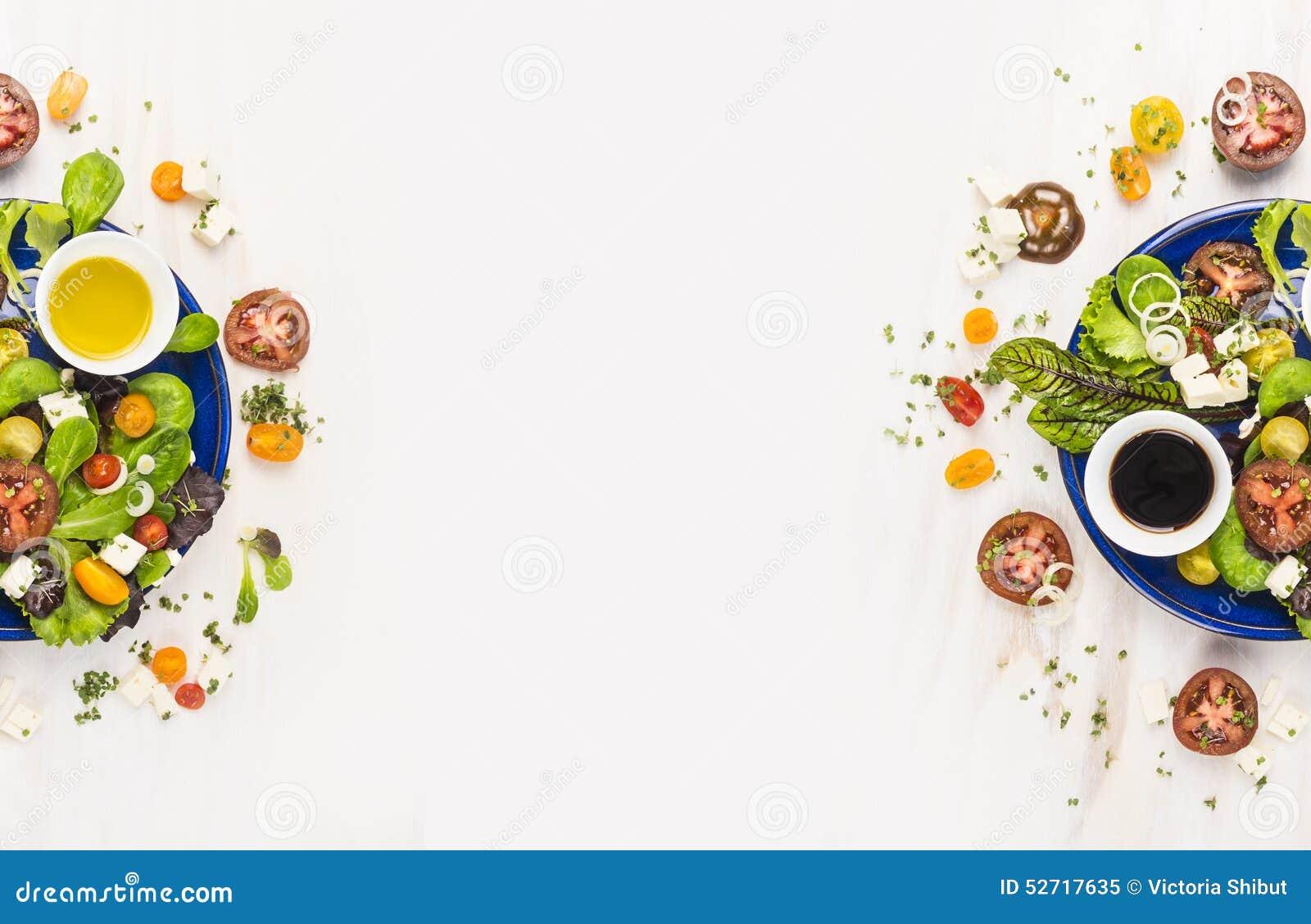 Salade avec des tomates, des verts, le habillage, le pétrole et le feta dans le plat bleu sur le fond en bois blanc, vue supérieu