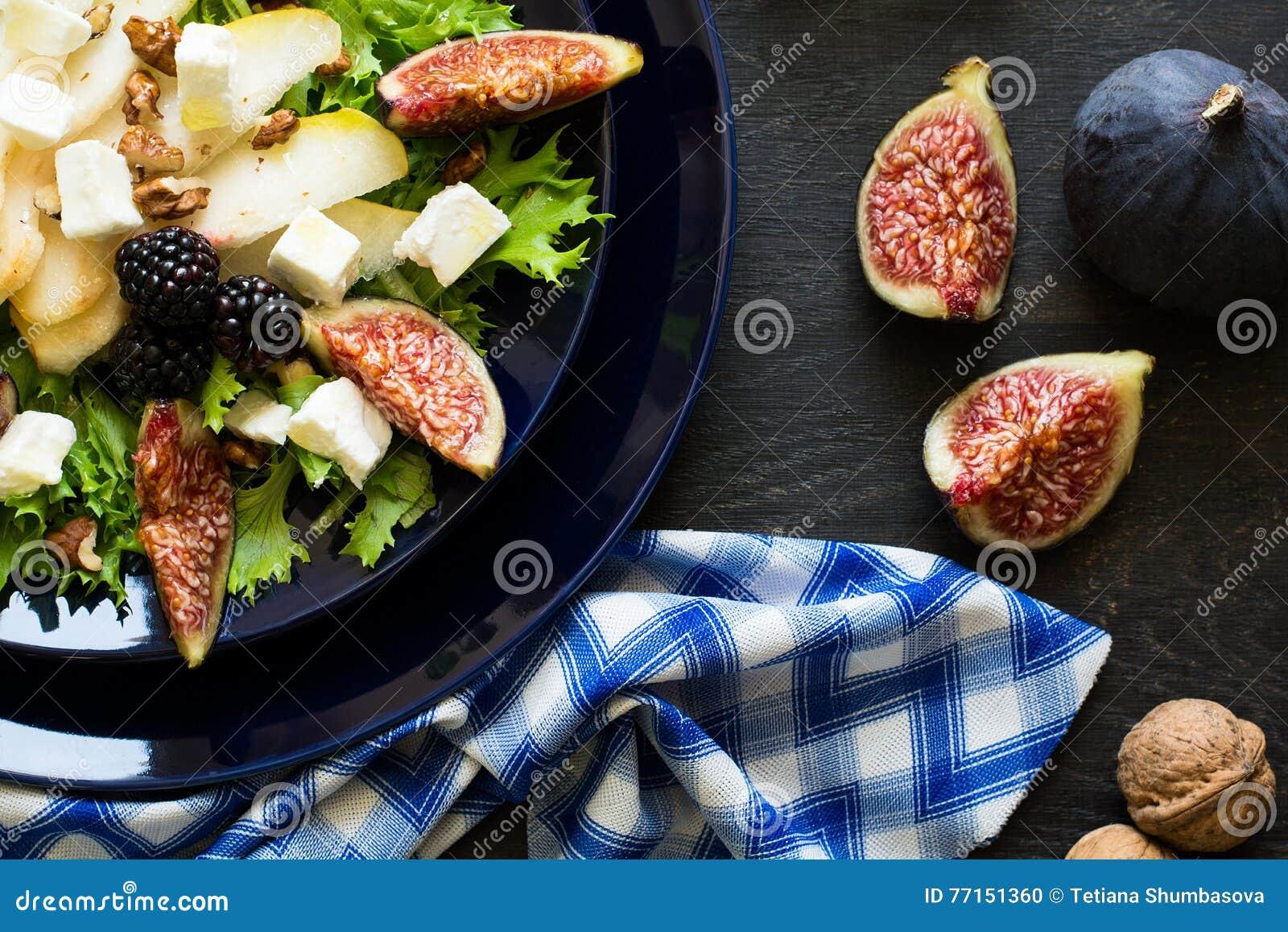Salade avec les poires, la laitue, les figues, les noix, le fromage de chèvre, les noix et le miel