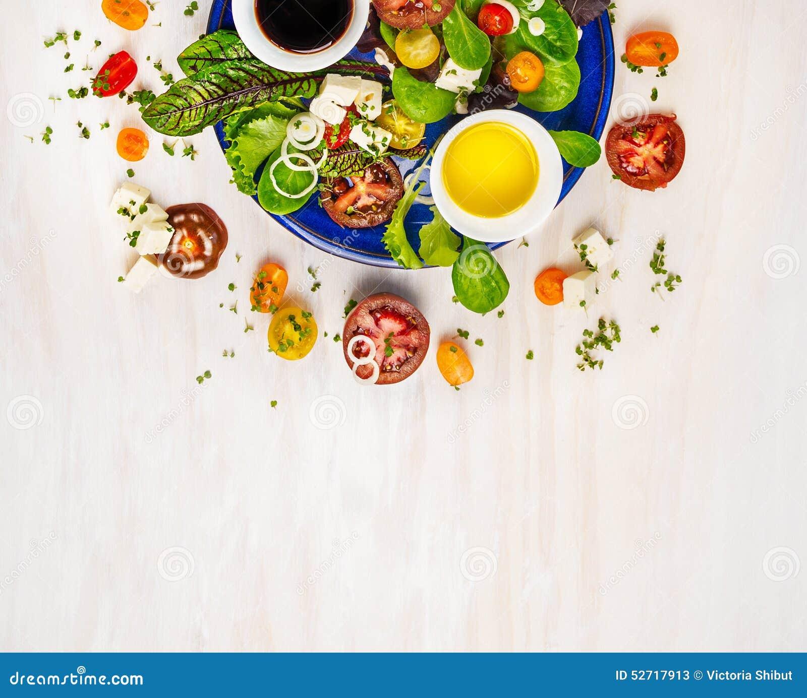 Salade avec les tomates, le feta, le vinaigrette balsamique de mustart et la variation de verts, du plat bleu